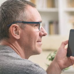 Man with a hearing aid uses his smartphone.