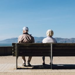 Older couple sitting together on a bench.
